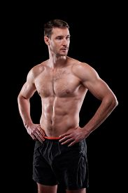 Young muscular shirtless male athlete keeping his hands on waist while standing in front of camera in isolation
