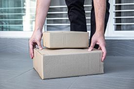 Man's Hand Holding Boxes At The Front Door To Receive Package, Shipping Delivery Concept