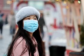 Moscow, Russia - January 2020: Chinese Girl In Protective Medical Mask Standing On A Winter City Str