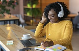 Smiling African American Girl In Wireless Headphones Looking At Laptop, Studying Foreign Language Th