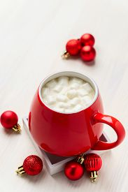 Red Mug With Hot Chocolate And Marshmallows With Christmas Decorative Balls On A White Table. Festiv