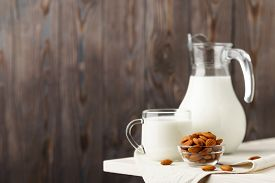 Almond Milk In A Glass Jug And Mug, Next To Nuts In A Bowl And A Textile Napkin On The Edge Of A Whi
