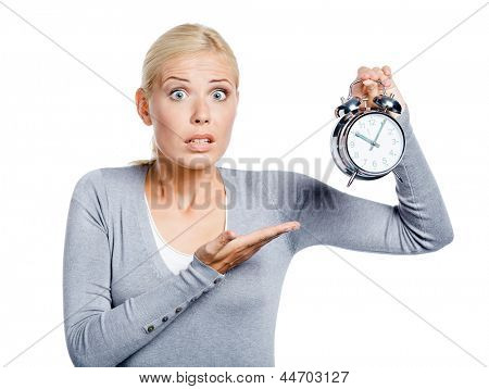 Worried woman in grey pullover pointing at the alarm clock, isolated on white