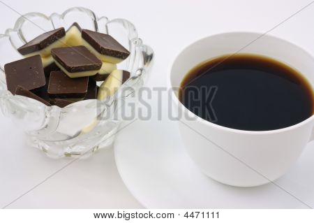 Coffee with a dish of sweet white and dark chocolate for a mid morning break. poster