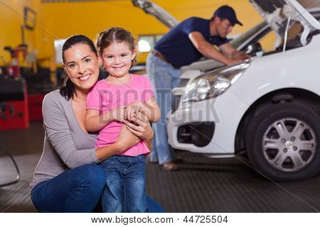 happy young mother and little daughter in garage waiting their car to be serviced