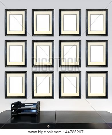 Twelve framed award certificates for employee of the month images on a wall in an office, in front of a file cabinet.