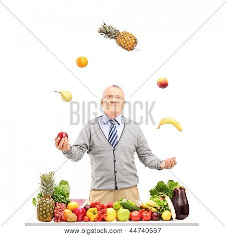 A smiling mature man juggling fruits behind a table full with fruits and vegetables, isolated on white background