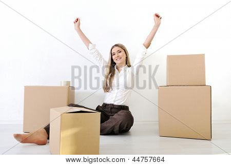 A young teen woman with heands up and belongings moving home