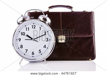 Alarm clock and briefcase isolated on white