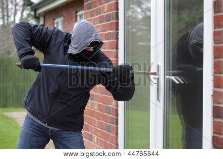Ladrón rompiendo una ventana de la casa con una palanca
