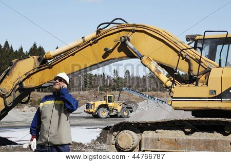 building worker directing bulldozers and trucks inside industrial area