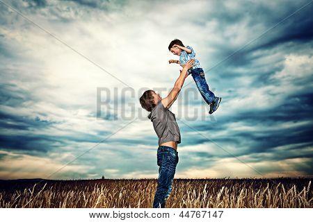 Glückliche Vater mit seinem kleinen Sohn im Weizenfeld über schönen bewölkten Himmel zu spielen.