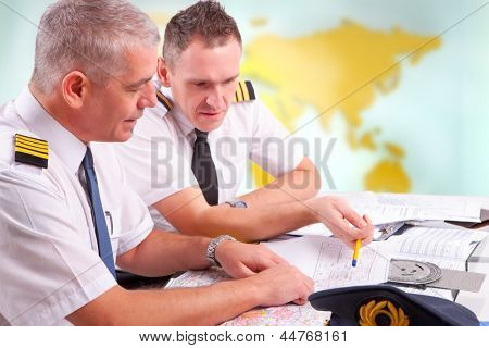 Two airline pilots preparing to flight, checking papers flight plan, log book. Pilots are sitting in AIS ARO Air Traffic Services Reporting Office poster
