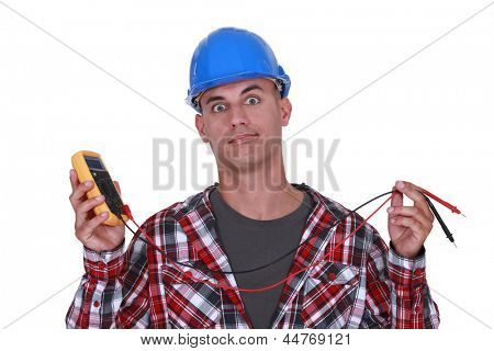 A wide-eyed tradesman holding a multimeter