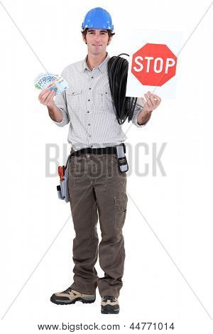 Electrician holding cash and stop sign