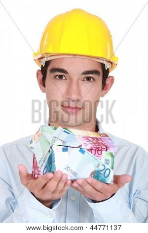 Tradesman holding a house made of money