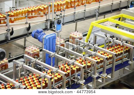 Top view of three lines with bottles of beer with red caps in beer factory.