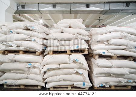 Rows of big white sacks at large warehouse in modern factory.