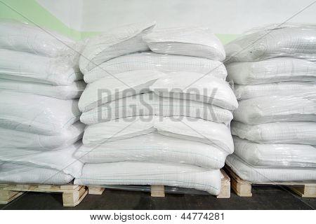 Three piles of big white sacks at large warehouse in modern factory.