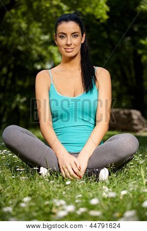 Pretty girl sitting in tailor seat, exercising in citypark, looking at camera.