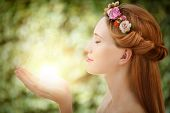 Beautiful fairy woman with glow in hands on natural green background poster