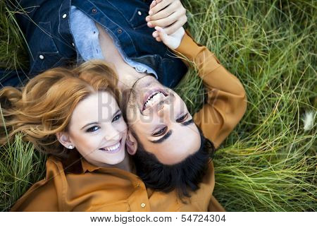 Above shot of a young couple in the countryside. She is kissing his cheek