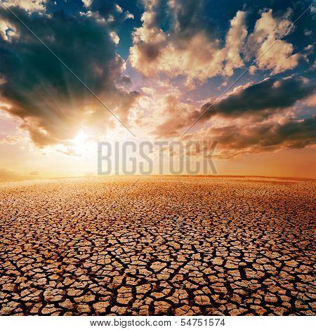 cracked desert and dramatic sunset