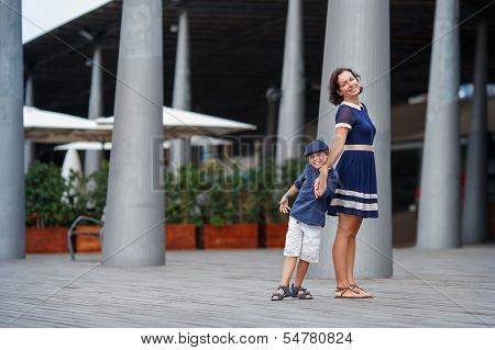 Young mother and her son walking outdoors in city