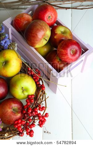 Juicy apples in box on white wooden table poster