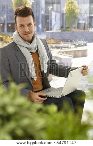 Young man using laptop computer sitting outdoors in citypark, removing usb flash drive.