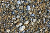 Variety of pebbles on a beach for use as a background poster