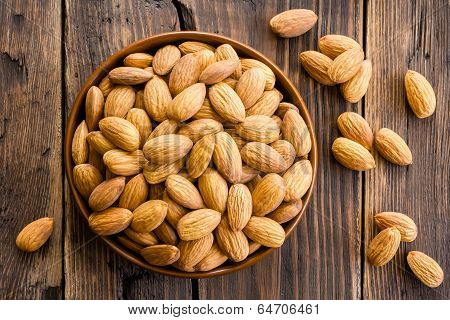 Almond kernels in a bowl on a wooden table poster