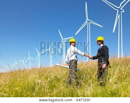 Engineers in field with plans building windmills poster