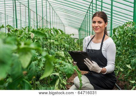 Attractive young female gardener in uniform