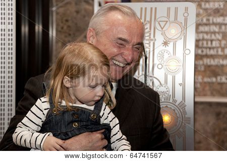 NEW YORK-APR 21, 2014: Police Commissioner William Bratton gets help from the daughter of an honored NYPD officer to light the Empire State Building in blue and purple for Police Memorial Week.