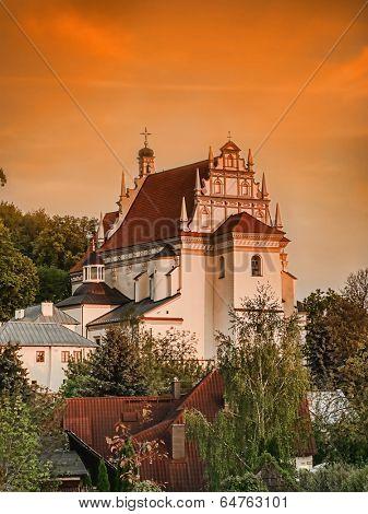 Historical Parish Church Fara in Kazimierz Dolny against sunset sky, Poland