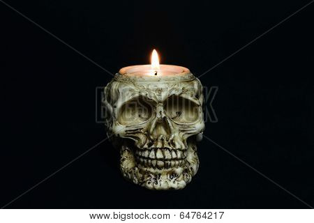 creepy skull candle on black background - front