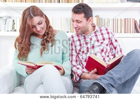 Cheerful Young Man And Woman Reading Different Books Together While Sitting Clode To Each Other