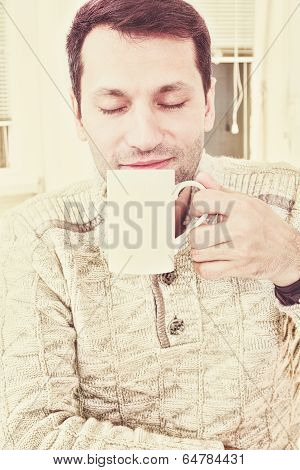 Good Looking Adult Man Savouring The Aroma Of A Cup Of Fresh Hot Coffee