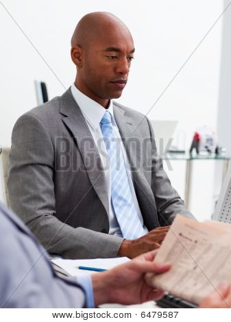 Businessman Reading A Newspaper With His Colleague Workig At A Computer