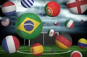 Footballs in various flag colours against football pitch under stormy sky poster