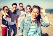 summer holidays and teenage concept - teenage girl in sunglasses and headphones hanging out with friends outside poster