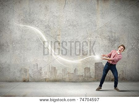 Young guy in casual pulling loop of light poster