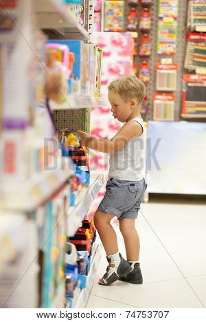 Boy watching cars in the toy shop