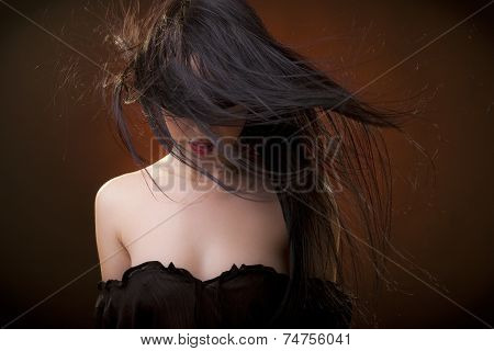 Beautiful sexy brunette woman in black erotic dress and hair in front of face
