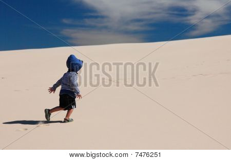 Toddler walking up sand dune