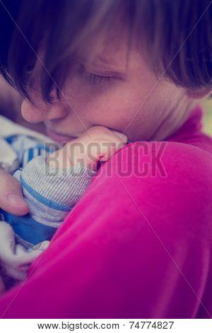 Loving Mother Cuddling A Newborn Baby