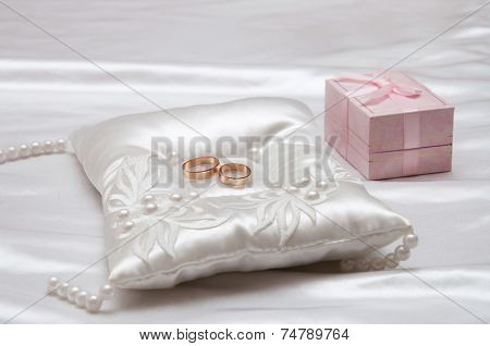 The wedding rings on a white pillow