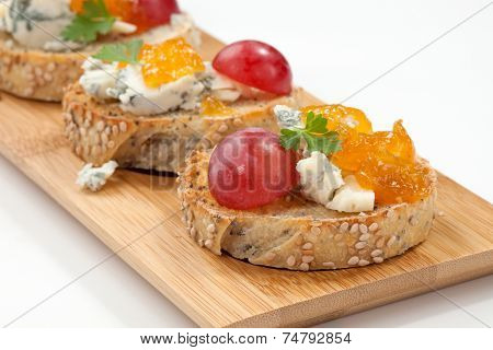 Blue cheese and apricot jam multigrain crostini with grapes and parsley on wooden tray. Apricote jam mini bowl. poster