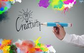 Businessman writing the word creativity and painting abstract colorful design on gray background concept for business idea, imagination and inspiration poster